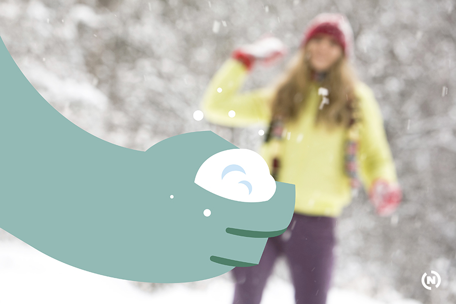 Portrait of woman throwing snow to man outdoor